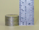 This photo shows 10 stacked dimes, which are approximately a centimetre thick.