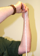 This photo shows someone measuring the length from his wrist to his elbow. This measurement is about a foot.